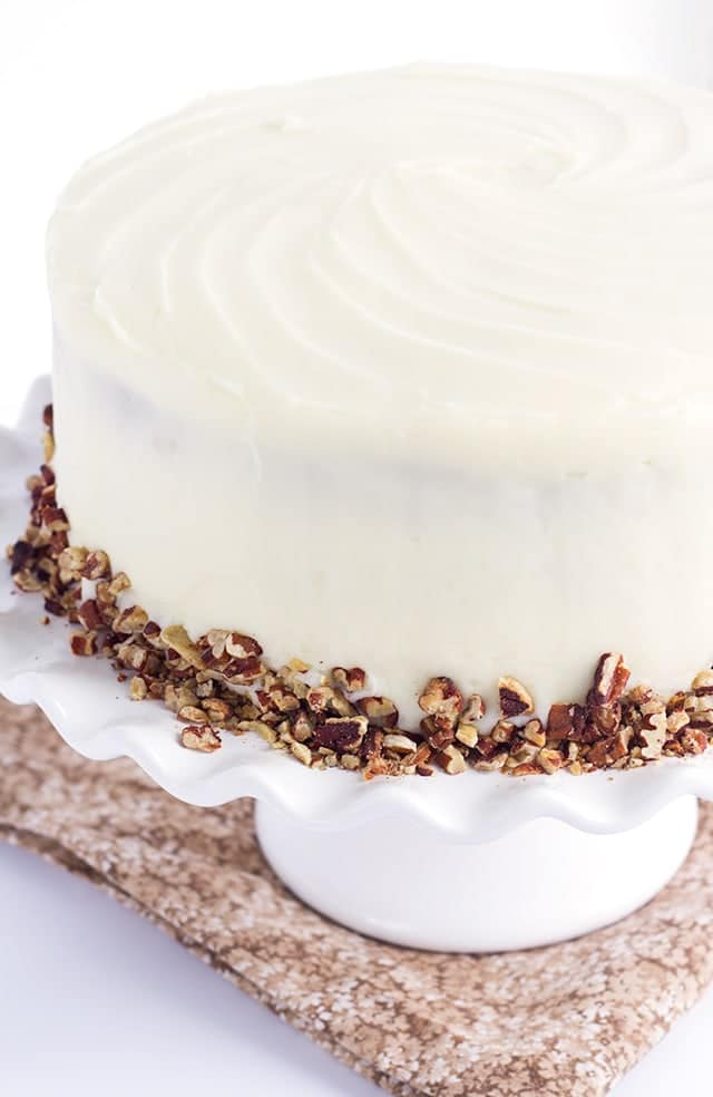 Pineapple Carrot Cake with Cream Cheese Frosting, garnished with toasted almonds, on a white cake stand.