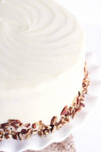 Carrot Cake with Pineapple and Cream Cheese Frosting, garnished with toasted pecans