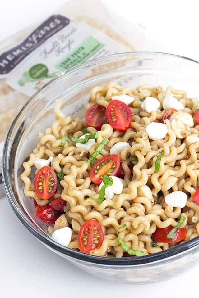 big salad bowl full of caprese pasta salad garnished with fresh cherry tomato halves