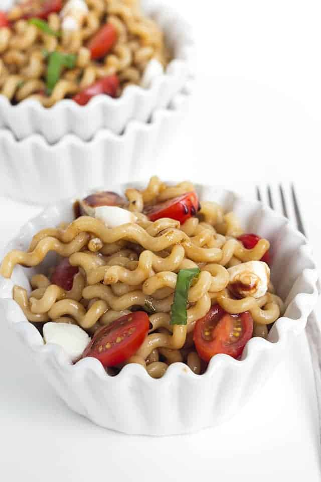 white ceramic bowls with scalloped rims are filled with caprese pasta salad