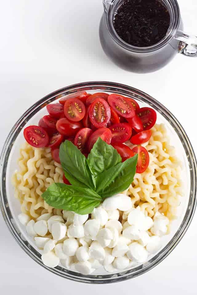 salad bowl filled with fusilli pasta, cherry tomato halves, fresh basil, and mozzarella pearls