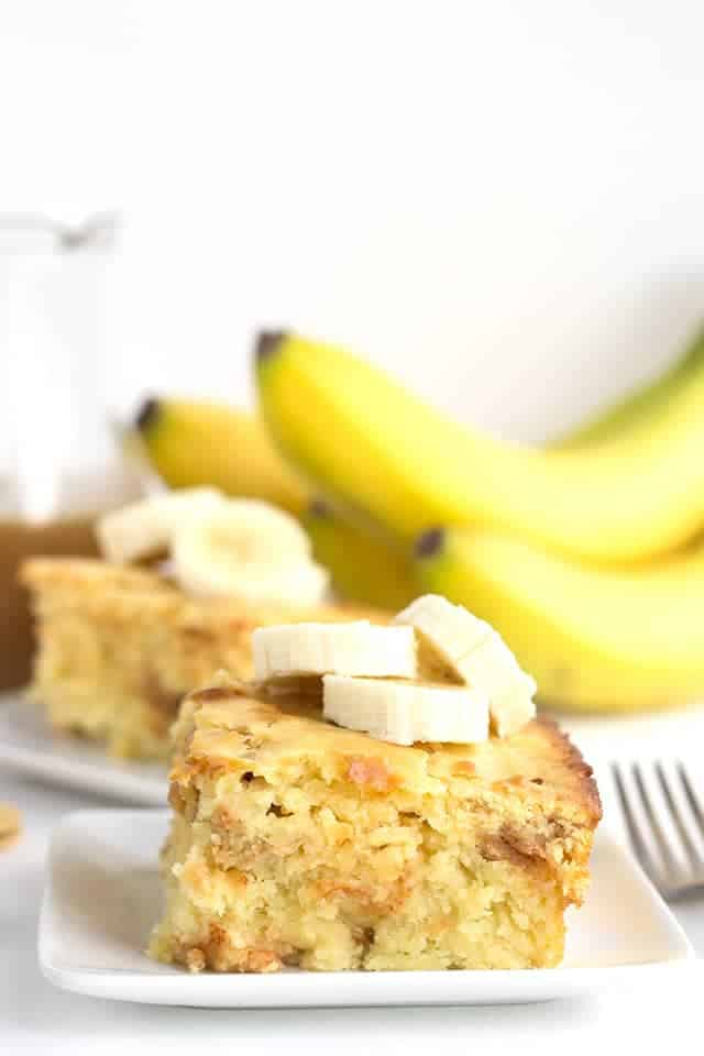 slice of bananas foster pancake casserole on a white plate with bananas