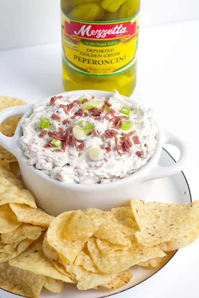 platter of tortilla chips and a bowl of Chipped Beef Dip with a jar of Mezzetta brand Peperoncini behind it