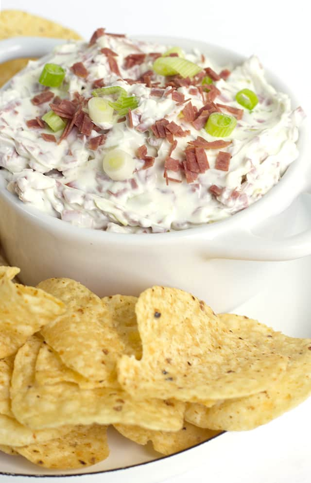 white bowl of Chipped Beef Dip and corn tortilla chips for dipping