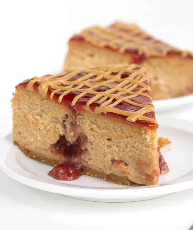 slice of peanut butter and jelly cheesecake on a white plate with jelly pouring out
