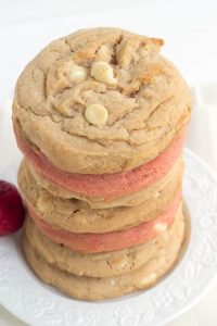 Strawberry Cheesecake Cookies - Tender white chocolate chip strawberry pudding cookies stuffed with a strawberry cheesecake filling.