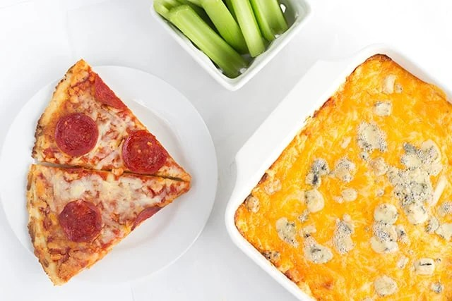 cheesy Buffalo wing dip next to slices of pepperoni pizza