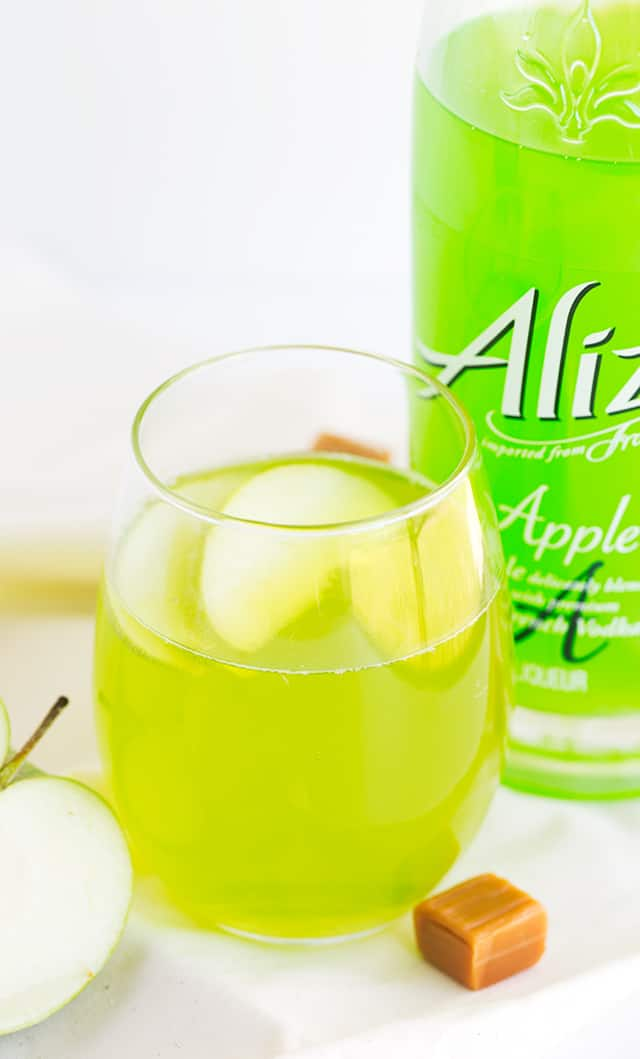 Caramel Apple Cocktail - how fun is a bright green drink that's caramel apple flavored?! This is a sweet cocktail that packs a punch from the liqueur. Garnish with a couple of apple slices and serve at your next party!
