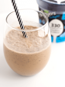 Glass partially filled with a coffee and cookies milkshake with a black and white striped straw.