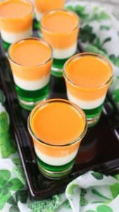 Overhead shot of St. Patrick'sDay Jello Shots on a black plate with a shamrock fabric