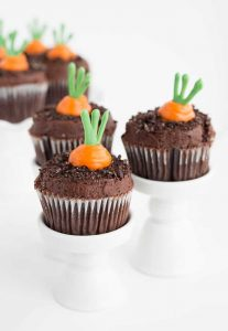 Three carrot patch cupcakes sitting on individual cupcake stands with carrot patch cupcakes on a ruffled white cake stand in the background