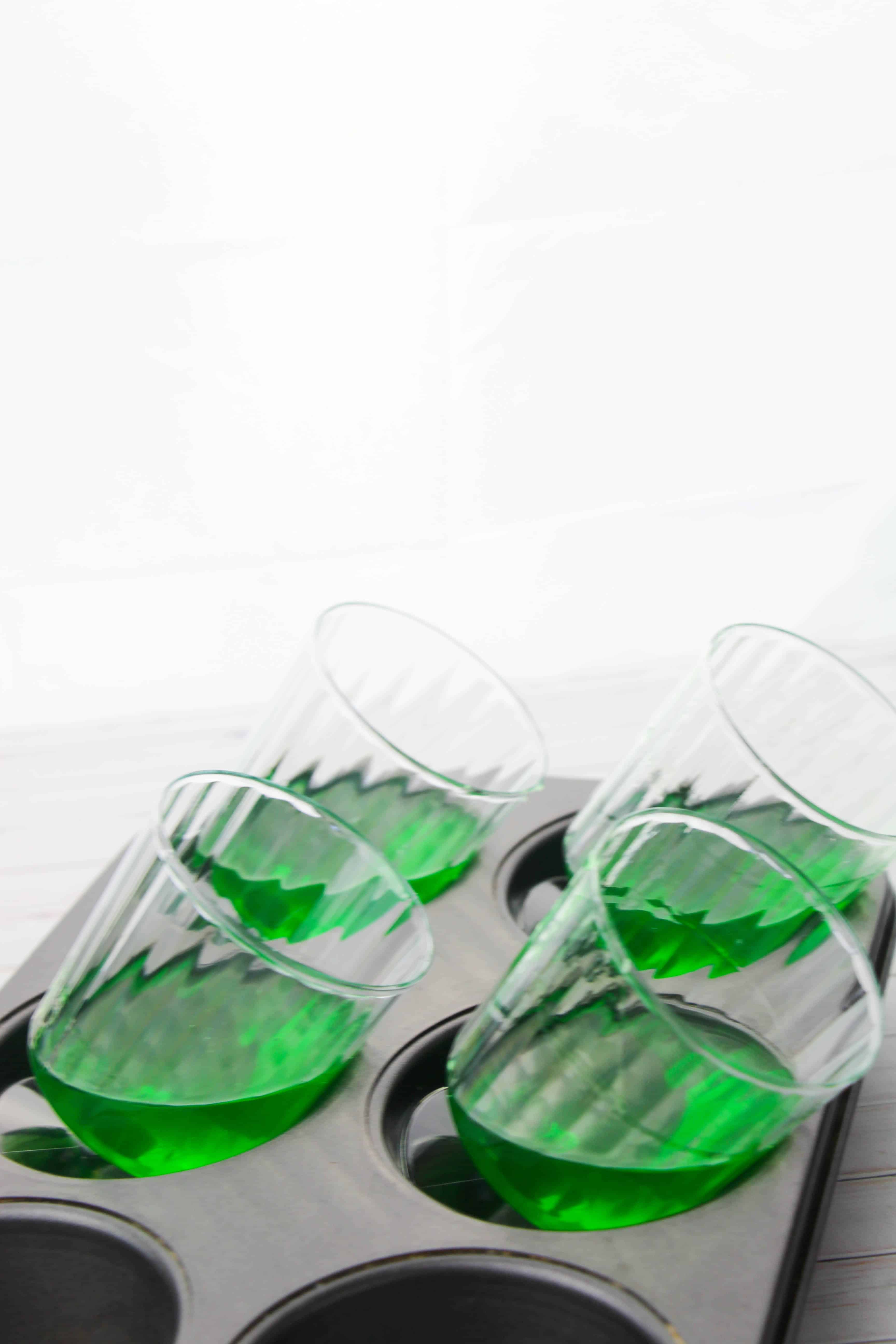 A photo of the glasses tipped to the side in a muffin pan with green jello setting up in them.