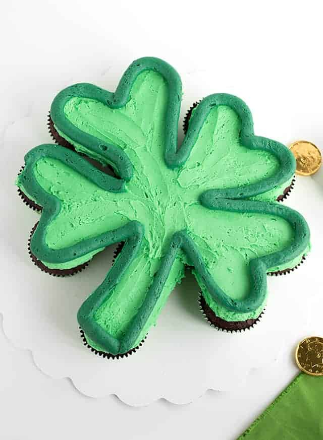 Shot at a 90 degree angle green shamrock cupcake cake with a dark green outline on a white cake board with gold chocolate coins scattered.