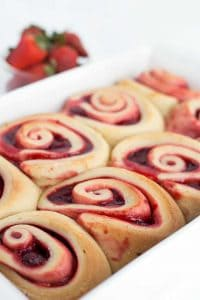 Strawberry sweet rolls in a white baking dish with strawberries in the background.