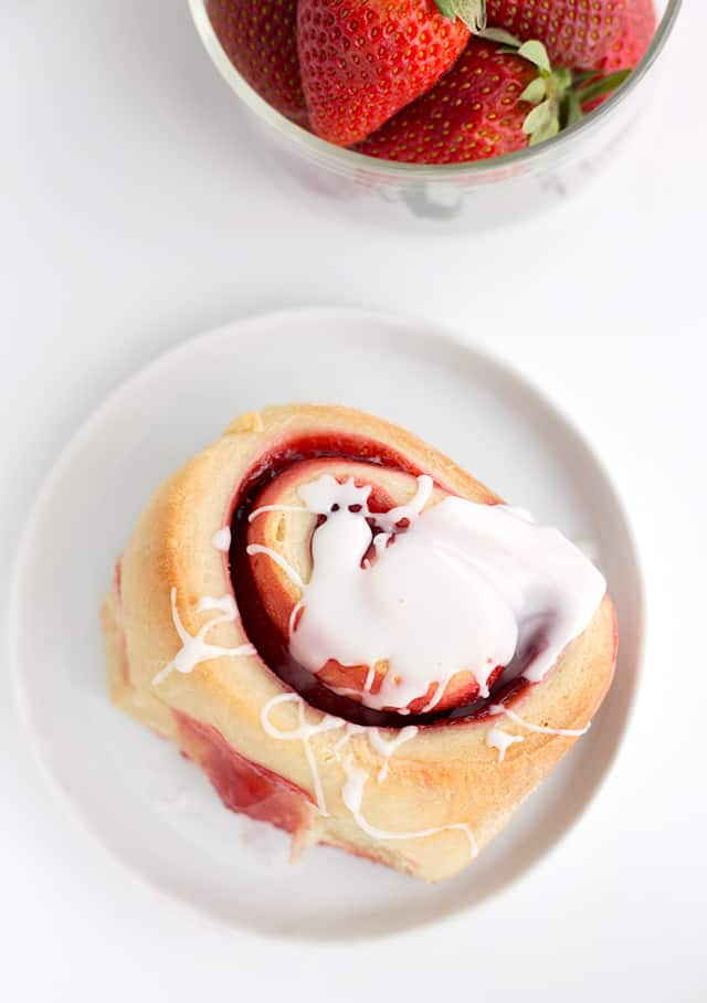 A strawberry sweet roll on a small white dish with glaze drizzled on top.