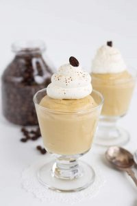 coffee pudding in glass serving cups with whipped cream on top