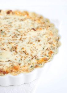 White pizza dip in a white ceramic tart pan.