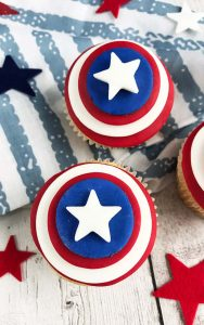 two 4th of july cupcakes close up with red and blue stars and a blue and white fabric in the background