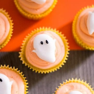 Ghost cupcakes with a dark wood and orange background