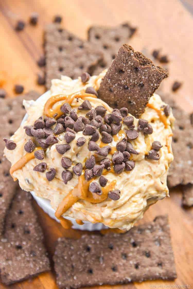 Bowl of no bake chocolate peanut butter cheesecake dip with chocolate graham crackers around it