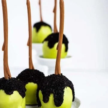 three Poison apple cake pops on a white plate