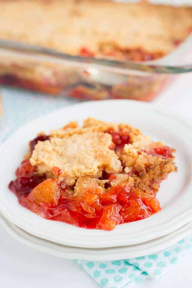 strawberry mandarin orange dump cake on a plate with glass pan