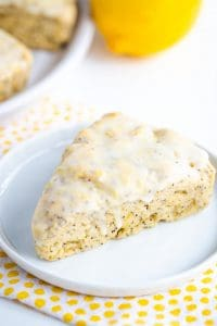 lemon poppy seed scone on white plate with polkadotted fabric