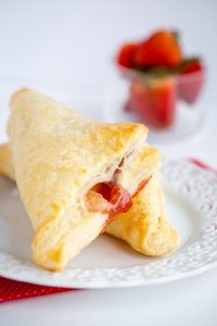 turnovers on a white plate with strawberries behind it