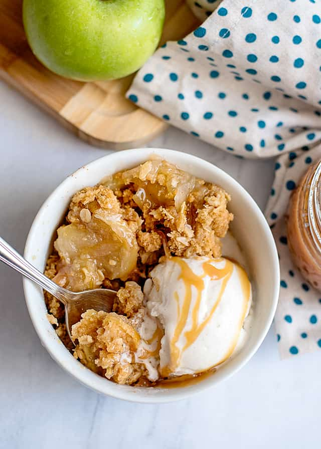 spoon in white bowl with caramel apple crisp, vanilla ice cream, and caramel sauce