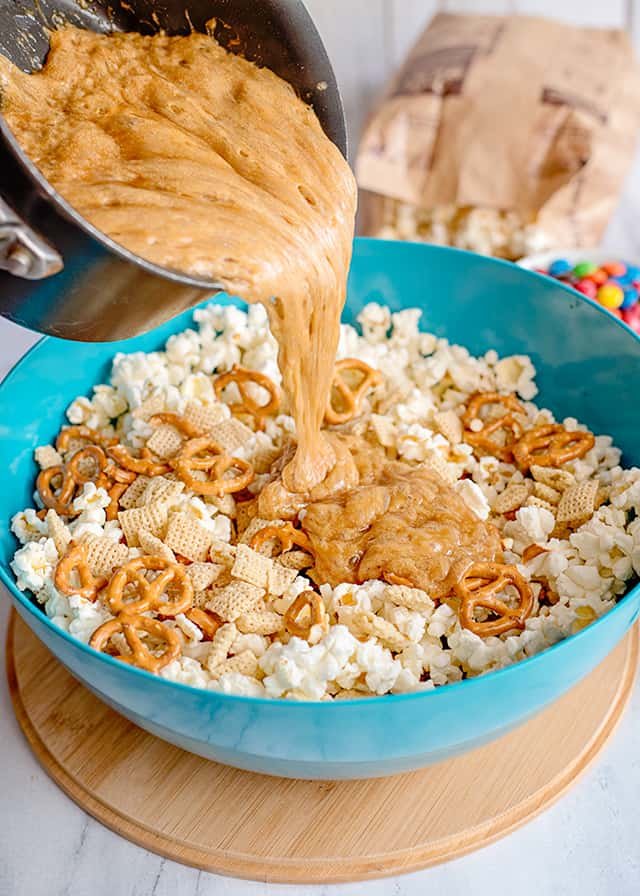 homemade caramel being poured into blue bowl with popcorn, cereal, and pretzels
