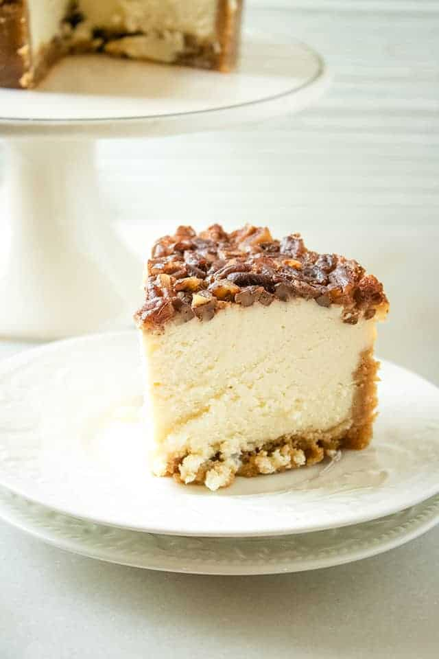 slice of instant pot pecan pie cheesecake on two white plates