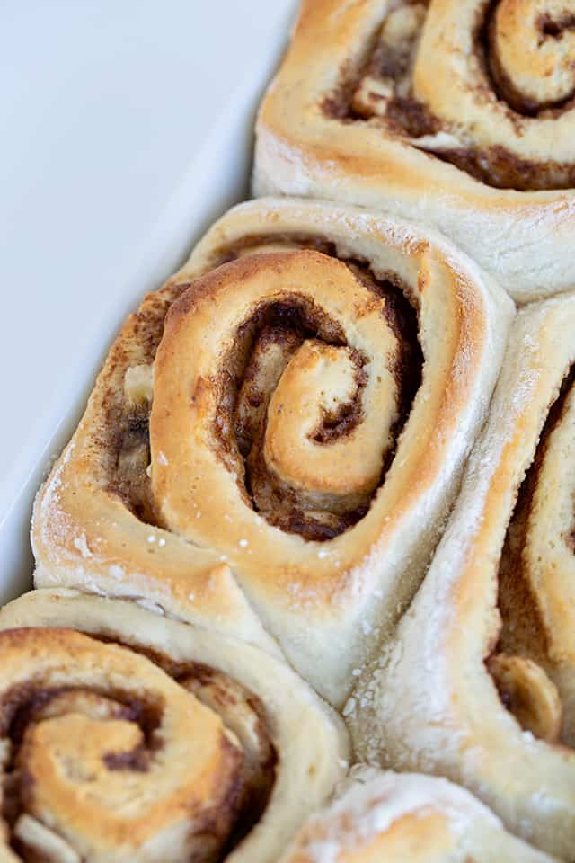Close up of pan of bananas foster cinnamon rolls without frosting