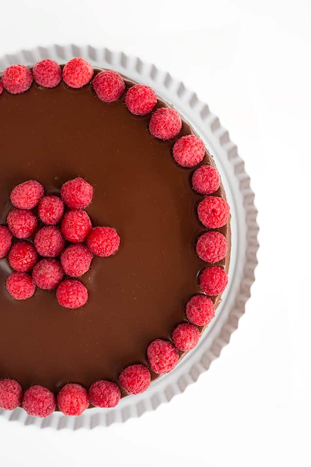 overhead view of whole chocolate raspberry cheesecake on white cake plate