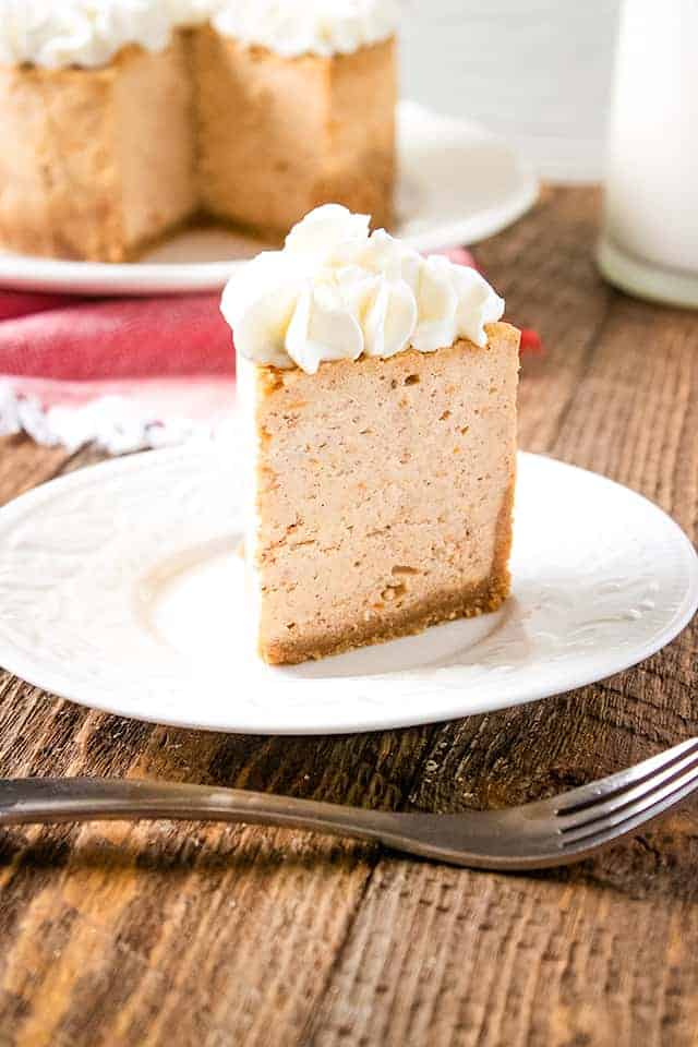 slice of instant pot sweet potato cheesecake on a white plate with fork