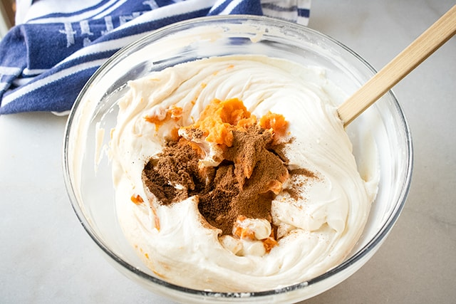 sweet potato cheesecake batter in a glass bowl with blue and white linen beside bowl