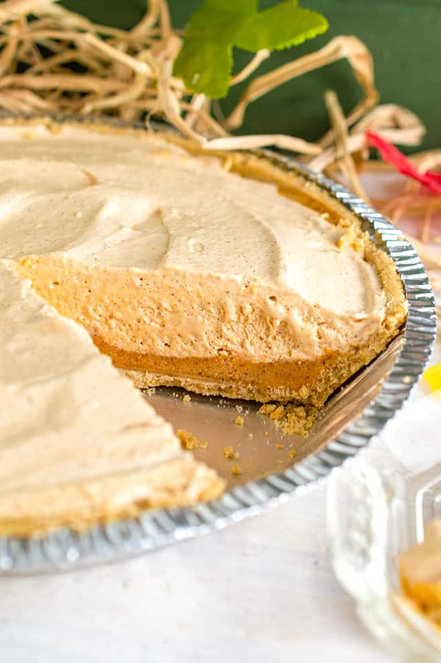 Pan of pumpkin ice cream pie with slice missing