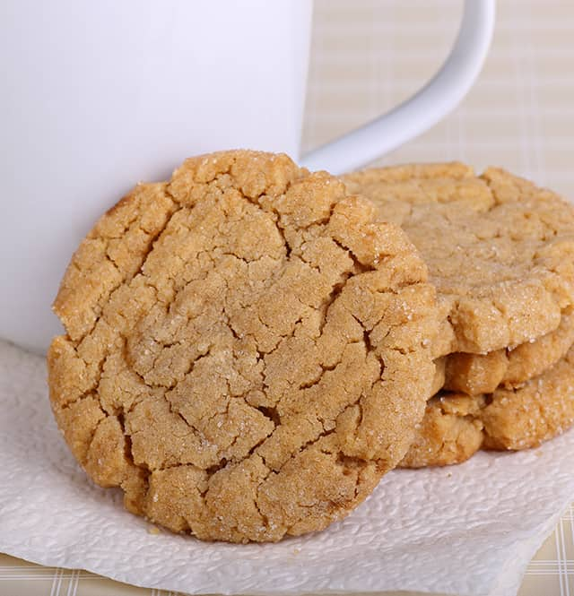 peanut butter cookies leaned against a white coffee cup