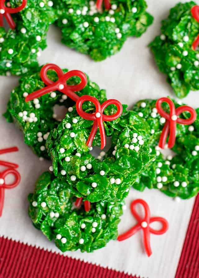 stacked christmas wreath cookies on parchment paper with red fabric underneath