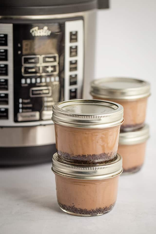 stack of sous vide cheesecakes in jars in front of Souspreme Multi Pot