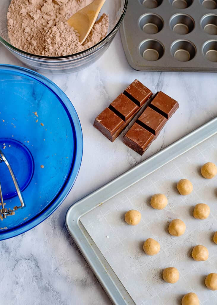 peanut butter balls on a baking sheet in a blue mixing bowl and almond bar next to the sheet