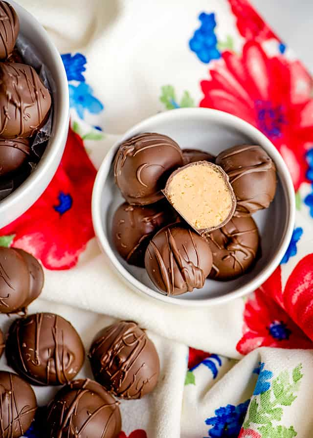 small bowl of peanut butter balls with other peanut butter balls scattered around it on a floral linen