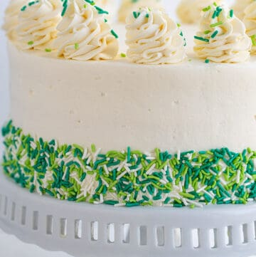 Cheesecake Cake on a white cake plate with green and white sprinkles