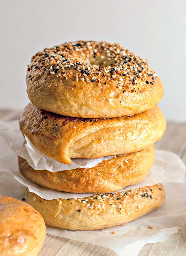 stack of homemade everything bagels with parchment paper between each one