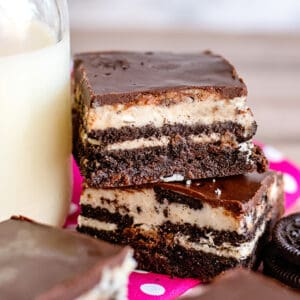 cookies and cream oreo brownies stacked on top of eachother next to a glass of milk with a pink fabric under them