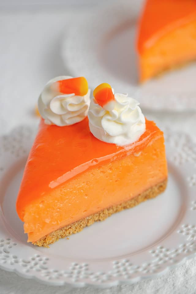 slice of candy corn cheesecake on a white plate with a second slice behind it