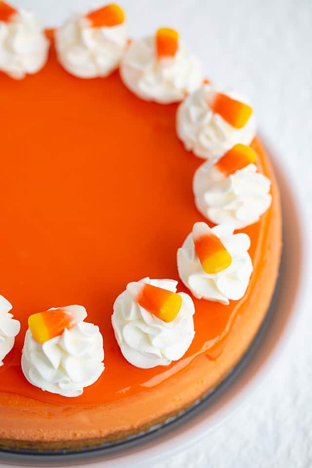 overhead photo of whole cheesecake focusing on whipped cream and candy corn pieces
