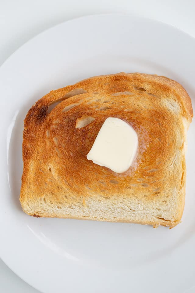 slice of toasted bread on a white plate with a dab of butter in the center