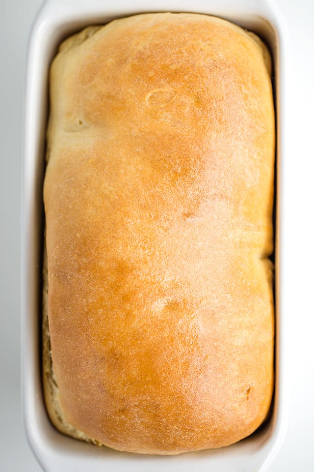 overhead photo of homemade bread in a white loaf pan