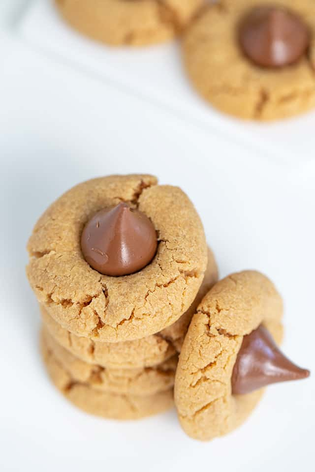 overhead closeup of stacked peanut butter blossom cookies on a white surface
