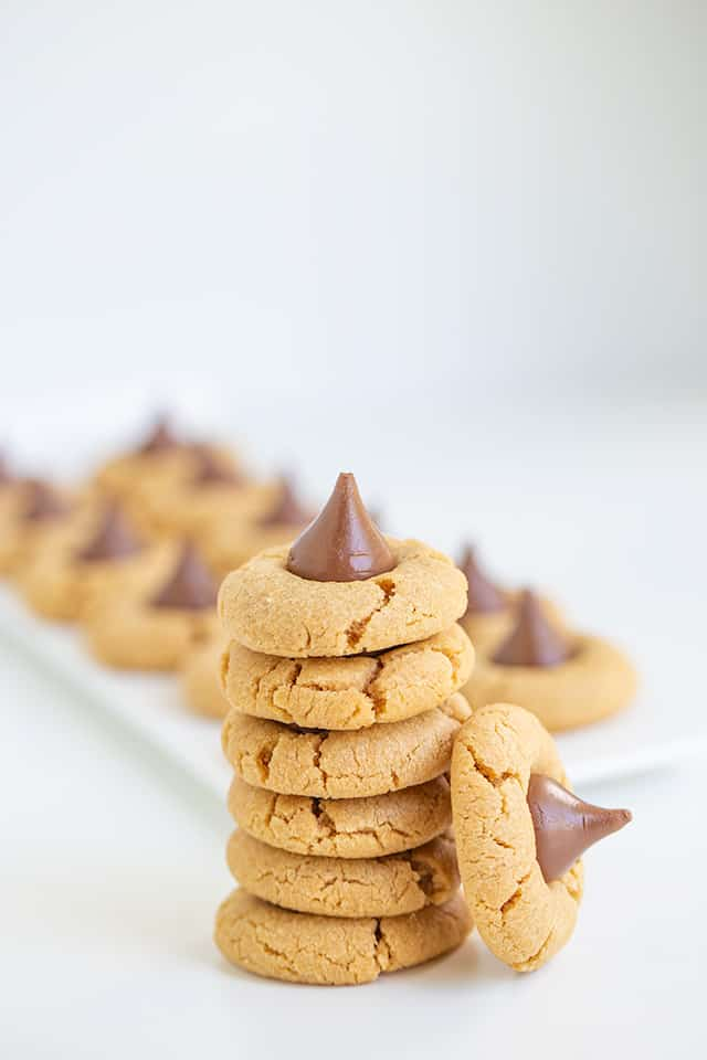tall stack of Hershey Kiss Cookies with a platter of cookies behind it